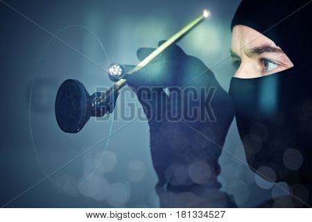 burglar with balaclava use circular glass cutter
