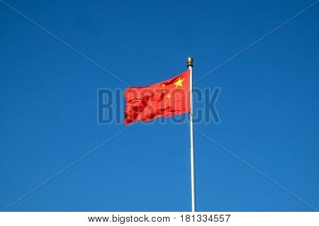 BEIJING, CHINA - FEBRUARY 23, 2016: Flag of China on the mast in Tiananmen Square. It's the third largest square in the world and important site in Chinese history, in Beijing, on February 23, 2016.