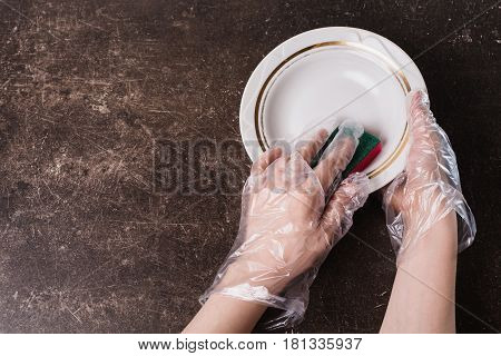 White dish detergent and sponge for dishes on a dark marble background. Hygiene. Wash dishes with gloves. Dish wash concept
