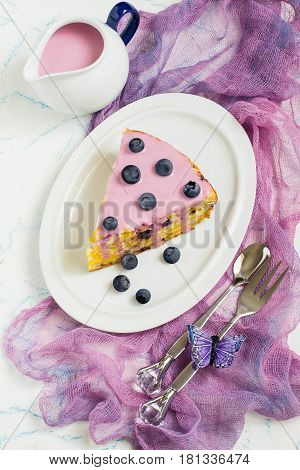 Delicious homemade pie with cottage cheese cornflakes and blueberries. The cake is cut into pieces served with berry-yoghurt sauce. Tasty breakfast. Top view