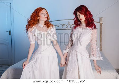 Two beautiful woman with red hair in a beautiful white wedding Victorian dresses on woman. Woman style. The fragile woman. Thin waist. Dress on woman. Red head woman. Lovely woman