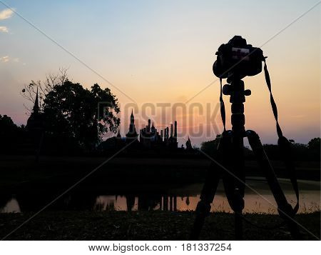Silhouette of camera on tripod and ancient ruin in Thailand against sunset sky. The temple named Wat Mahathat part of Sukhothai historical park ancient kingdom in thirteenth centuries.