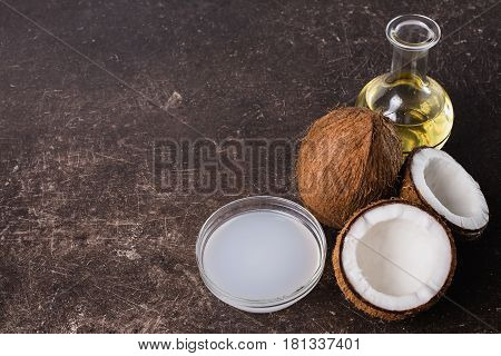 Coconut and coconut milk on a dark marble background. Exotic large walnut with milk. Personal care. Spa treatments with milk and coconut