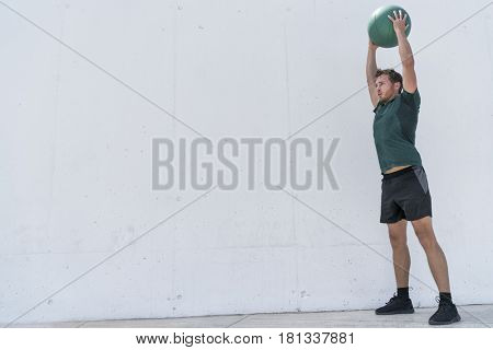 Fit man throwing medicine ball against gym floor upper body workout exercise. Cross training at fitness center.
