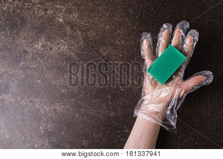 Hand in plastic hygienic gloves with a sponge on a dark marble background. Tidy up the house. Wash the dishes. Man hand. Woman hand concept. Hand with sponge