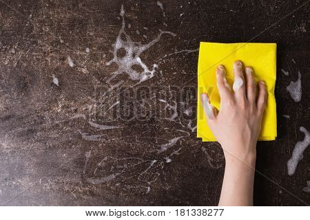 A hand with a rag on a dark marble background. Tidy up the house with rag. Putting things in order. Rag in hand concept. Man hand