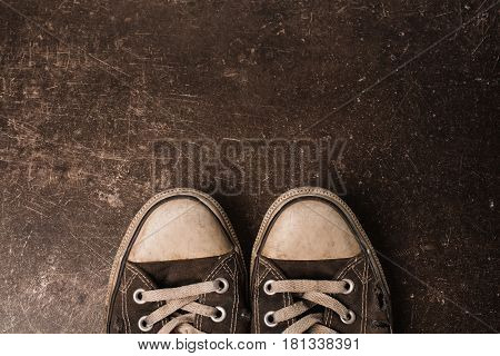 Footwear concept. Old black sneakers on a dark marble background. Footwear for outdoor activities. Dark footwear