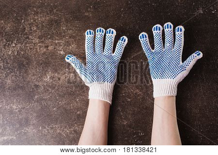 Hand in working gloves on a dark marble background. Tidy up the house. Do makeovers. Hand concept. Hand on dark table. Workplace with hand