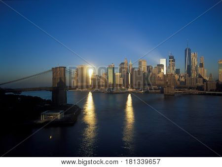 Manhattan skyline with Brooklyn Bridge at sunrise.