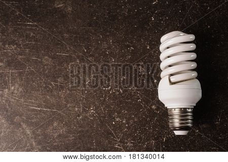 Fluorescent light bulb on a dark marble background. To save energy. Eco concept fluorescent light lamp