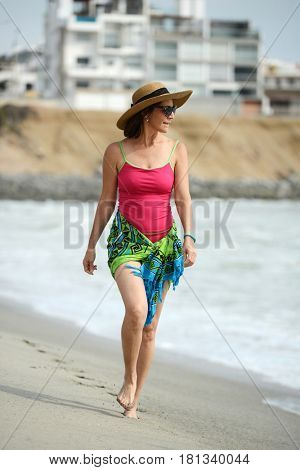 Middle age woman walking by the shore and looking away