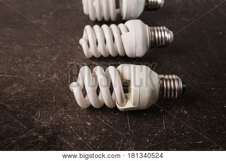 Fluorescent light bulb on a dark marble background. To save energy. Eco concept with fluorescent light lamp
