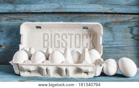Chicken eggs in a cardboard box on a wooden table