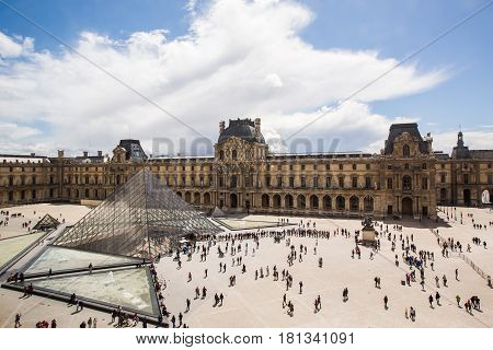 Louvre the largest museum in the world. Louvre Pyramid. Travel through Europe. Attractions in France. Sunny Paris. Clouds in the clear sky. People silhouettes. Long queue to the museum