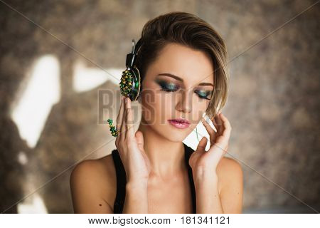 Lovely blonde girl with tanned skin and white hair listening to music on headphones. Blonde female beauty portrait of a beautiful makeup. Enjoying good music. Blonde model
