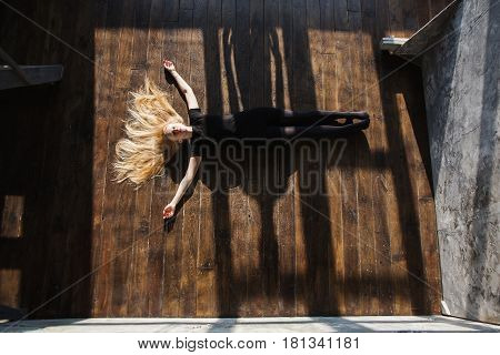 The girl with long blonde hair on floor. Woman lying on the floor with arms outstretched. Hard shadows on floor