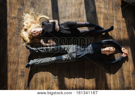A young man and young blonde woman with long hair lying on the floor. Problems and difficulties in relations. The difficult situation in life. Conceptual photography. Actor play. Hard shadows. Conflict situation. Conflict concept