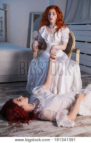 Two sensual beautiful girls with red hair in a beautiful white wedding Victorian dresses. Female style. The fragile sensual girl. Thin waist. A  sensual woman sits on a chair. Conceptual photography. Sensual girl lies on the floor