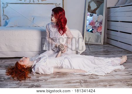 Two beautiful authentic girls with red hair in a beautiful white wedding Victorian dresses. Female style. The fragile girl. Thin waist. Authentic woman sits on a chair. Conceptual photography. Authentic girl lies on the floor