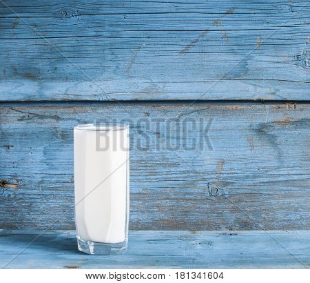 Glass of milk on wooden table.
