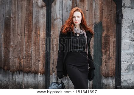 Attractive striking girl with long red hair in black clothes. Attractive woman in a black coat and backpack in hands posing on the background of old wall. Female street fashion style. Beautiful attractive elegant redhead model