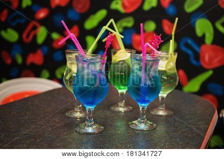 Blue and green cocktail in a glass with ice and a straw on the table. Cocktail in a glass. Cocktail in the bar on the table