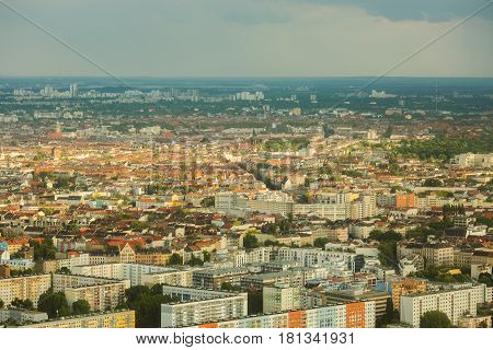Travel to Germany. View to  skyline of the houses and streets of Berlin with a bird's-eye view. Overcast sky. Light from the sun on the houses. Residential houses. Megapolis. European city.   skyline of the city of the city