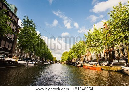The capital of the Netherlands. Spring in the Netherlands. Spring sunny Amsterdam. The bright clear blue sky with white clouds. Boat trip on the canals of Amsterdam. The bridge over the water. Travel to netherlands