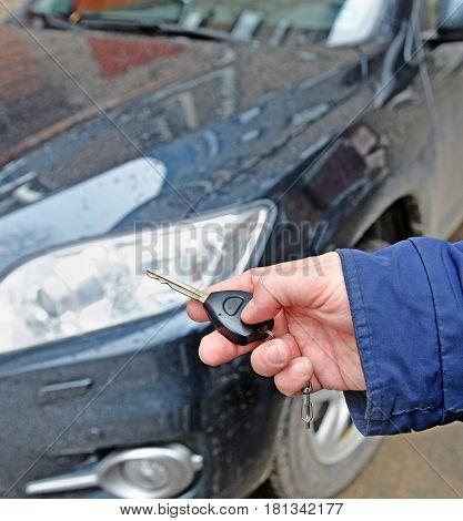 Man's hand holds car key against of dark auto