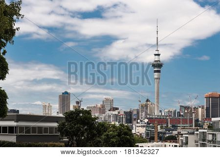 Auckland New Zealand - March 1 2017: From the higher lying Ponsonby Road the Sky Tower can be seen clearly towering over the rest of the skyline with famous business names. White clouds in blue sky
