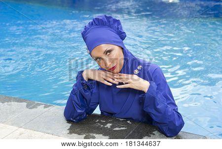 attractive woman in a Muslim swimwear burkini in the pool