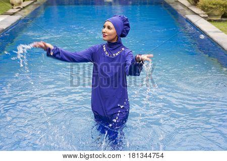 attractive woman in a Muslim swimwear burkini splashes water in the pool