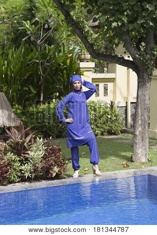 attractive woman in a Muslim swimwear burkini stand on a pool side in a tropical garden