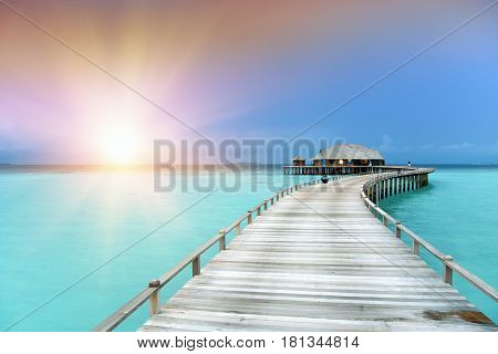 The wooden road over the sea to the tropical island