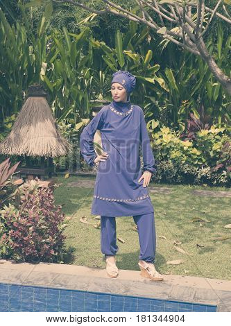 attractive woman in a Muslim swimwear burkini stand on a pool side in a tropical garden toning