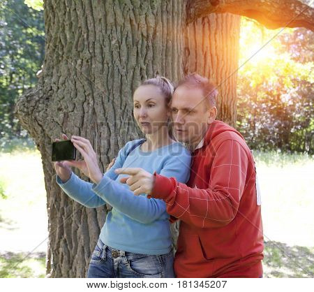 man and woman near an oak in summer day show to the side and photograph on phone