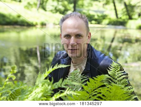 summer portrait of the mature man through fern leaves on a background of the forest lake
