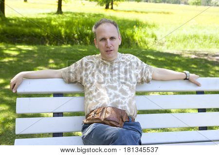 summer portrait of the mature man on a bench in the park