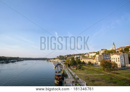 BELGRADE SERBIA - OCTOBER 9 2016: View of Sava river bank in Belgrade. An orthodox cathedral church can be seen on the right Kalemegdan fortress on the background