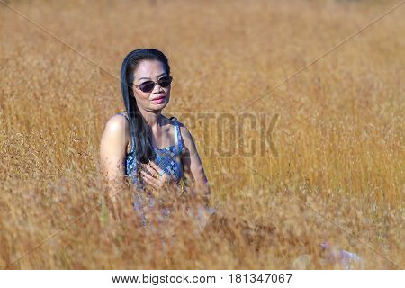Woman relax outdoor in field Utricularia delphinoides Thor.ex Pell. flower at Mukdahan Nation Park Thailand