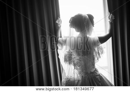 Beautiful bride with white veil posing looking out the window morning preparation for wedding ceremony. Young gorgeous model in bride's dress in full length