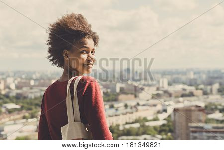 Portrait of young beautiful cute mixed Brazilian teen girl with curly afro hair standing on observation point very high and half-turned to camera sunny summer cityscape below in blurred background