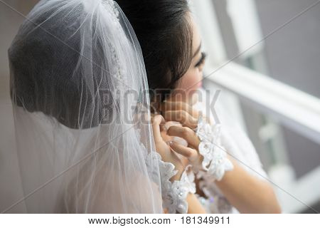Beautiful brides in white wedding dress put on luxury earrings morning wedding preparation bride with earrings close up