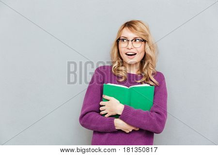 Glad young woman with opened book looking away isolated