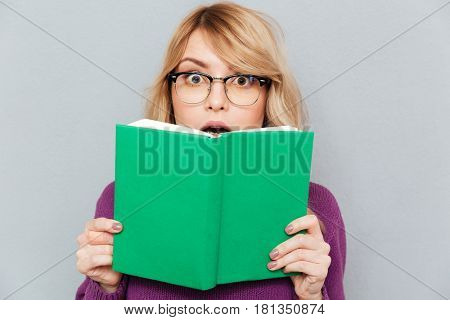 Shocked young blonde woman hiding face with green book isolated