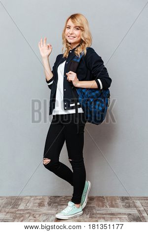 Picture of happy young lady with backpack posing over grey wall and make okay gesture. Looking at camera.
