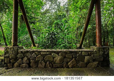 Two big pillar standing on stone wall of a gazebo in the middle of green garden photo taken in Jakarta Indonesia java