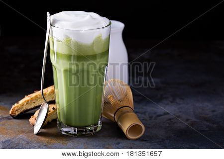 Matcha latte with milk foam in tall glass with biscotti