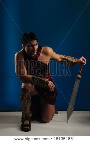 The tough warrior is kneeling down with a sword.