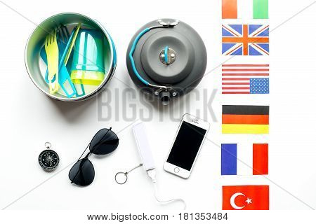 Traveler's accessories, power bank and flags in vacation concept on white table background top view